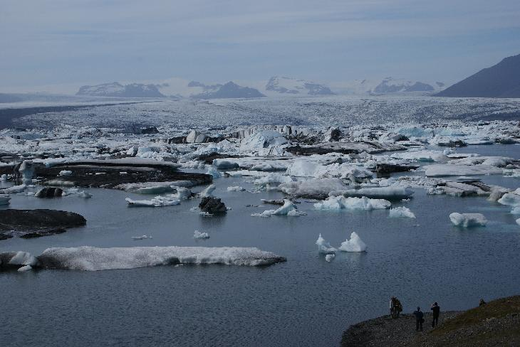 Landscape view of icebergs in the Jökulsárlón (Jokulsarlon) glacier lagoon. In the distance is the Breiðamerkurjökull glacier branching from the larger Vatnajökull glacier.