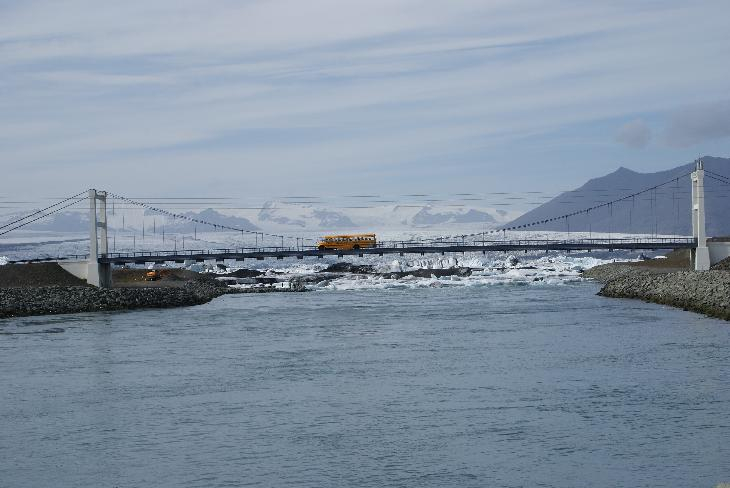 Photo of a school bus crossing a bridge at the Jökulsárlón glacier lagoon in Iceland.  In the distance is the Breiðamerkurjökull glacier branching from the larger Vatnajökull glacier. Vatnajökull also contains the volcano Grimsvotn. (Grímsvötn)