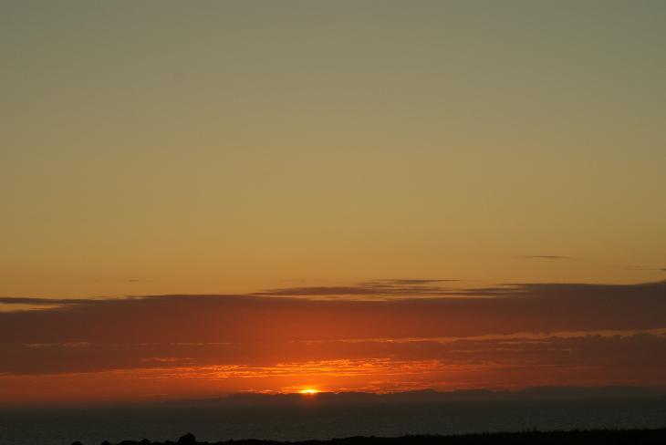 A photo of the sun on the horizon at midnight in June.  Taken near Reykjavik Iceland.