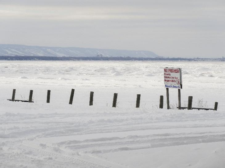 A winter landscape view of Wasaga Beach and the Blue Mountains of Collingwood Ontario Canada.  Photo was taken from the beach area 6 location of Wasaga Beach, across a frozen Georgian Bay.