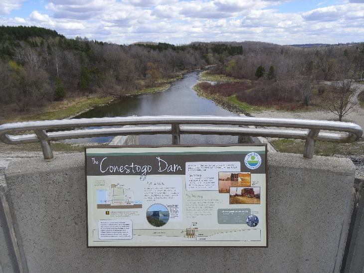 Looking southeast.  View of Conestoga River from the top of the Conestoga Dam bridge.  In the foreground is the information sign of the dam.