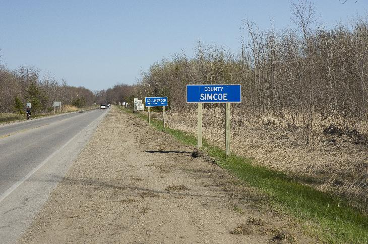 Sign of at entrance to Simcoe County travelling eastbound on Highway 26.  Collingwood population sign is in the background.  Collingwood population stating 17500 inhabitants.