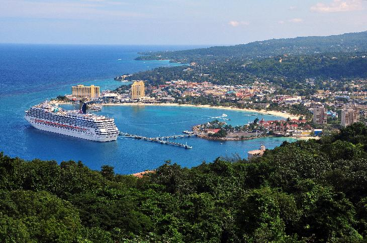 Photo of Carnival Freedom Cruise Ship docked at the Ocho Rios port.  View of Ocho Rios beach and skyline in background.