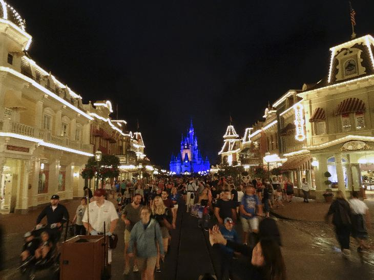 This is an evening view of Main Street USA and Cinderella Castle, at Magic Kingdom Disney World Florida.  The castle is blue, as this is following the evening fireworks show, with most people heading home.