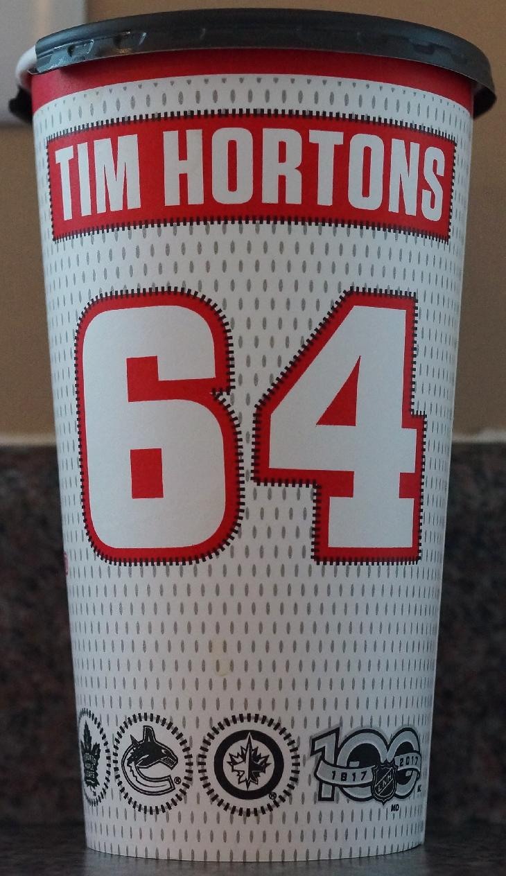 The back of the Tim Hortons large NHL 100 coffee cup in fall 2017. This is the Canadian version, found in Ontario.  The 64 signifies the year that Tim Horton established the first donut shop.