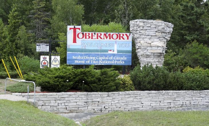 The Tobermory welcome sign, along Highway 6.  A replica of a flowerpot is set beside the sign.