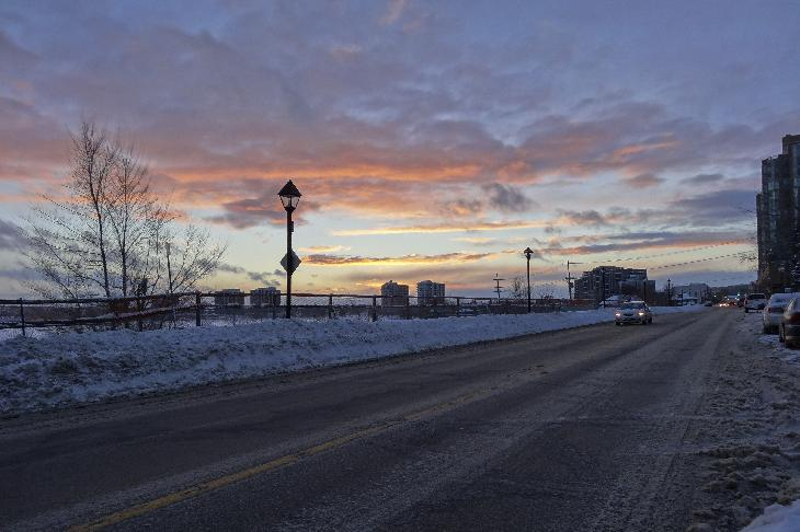 Photo of a January sunset at 5pm. Looking west on Dunlop Street in Barrie Ontario, along Kempenfelt Bay and Lake Simcoe. Downtown Barrie can be seen along the street.