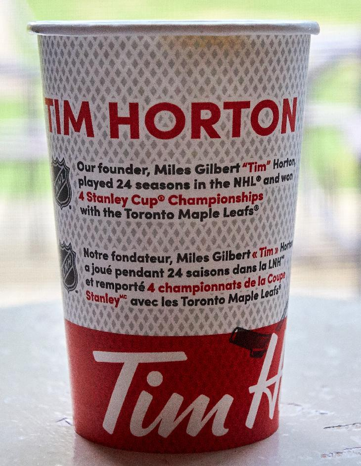 The front of the Tim Hortons medium coffee cup in fall 2018. Depicts a bio of Tim Horton himself. States that their found is Miles Gilbert 'Tim' Horton. This is the Canadian version, found in Ontario.