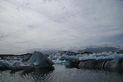 Photo of icebergs in the Jökulsárlón (Jokulsarlon) glacier lagoon. In the distance is the Breiðamerkurjökull glacier branching from the larger Vatnajökull glacier.  Vatnajökull also contains the volcano Grimsvotn. (Grímsvötn)