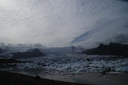 Fjallsárlón is a glacier lake at the south end of the Icelandic glacier Vatnajökull. Fjallsjökull which is part of the bigger glacier reaches down to the water of the lake and some ice-bergs are drifting by on its surface.