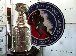 Photo of the Stanley Cup on display at the Hockey Hall of Fame.  Amongst the plaques of all the hall of fame members.