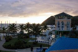 Photo of the beach and main pool at Sandals Grande St. Lucian Resort and Spa.  Sun setting behind pitons.