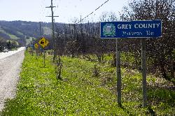 Photo of Grey County welcome sign travelling west on County Road 19 in Grey County.  Near intersection of County Road 19 and Osler Bluff Road. The Blue Mountains are in the background.