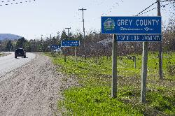 Photo of Grey County welcome sign, The Town of the Blue Mountains population sign, and Craigleith limits sign, travelling west on County Road 19 in Grey County.  Near intersection of County Road 19 and Osler Bluff Road. The Blue Mountains are in the background.