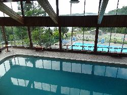A view of the pools and shoreline at Hidden Valley Resort in Huntsville Ontario.  Shown are the indoor pool, the outdoor pool below, and shoreline in the distance.