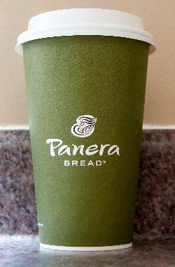 The front side of a Panera Bread paper coffee cup.  This is a 2017 edition of the cup.  Olive color with white markings.
