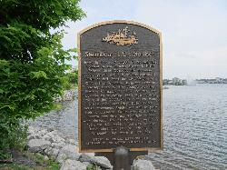 A photo of a memorial plaque erected along the shores Lake Simcoe at Kempenfelt Bay in Barrie. Honour Joseph C. Morrison, who was president of the Ontario, Simcoe and Huron Railroad Union Company.  Depicts an illustration of a sidewheel paddle vessel build in 1854.  In 1857 the steamboat took fire and sank.