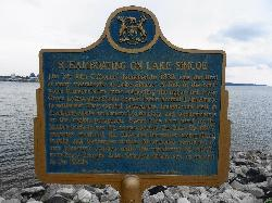 A photo of a memorial plaque erected along the shores Lake Simcoe at Kempenfelt Bay in Barrie. Describe how the 'Sir John Colborne' steamboat Launched in 1832 as one of the first of many steamboats on Lake Simcoe.  Installed by the Ontario Heritage Foundation.
