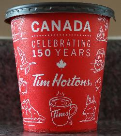 The English side of the Tim Hortons medium coffee cup celebrating Canada's 150th anniversary in 2017. Purchased in Ontario.  Contains iconic images of Canada.