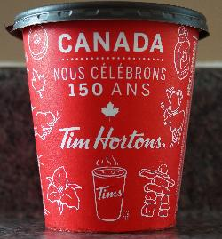 The French side of the Tim Hortons medium coffee cup celebrating Canada's 150th anniversary in 2017. Purchased in Ontario.  Contains iconic images of Canada.