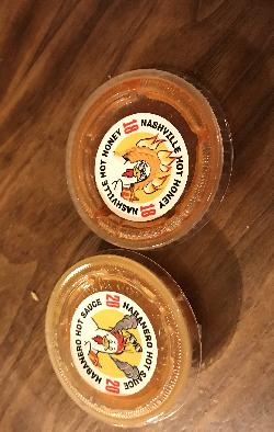 A sample of hot sauces available at Chicken Guy n Disney Springs, Orlando Florida.  These particular sauces are number 20 Habenero Hot Sauce and number 18 Nashville Hot Honey.  The Chicken Guy is Guy Fieri.